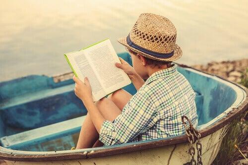 bambino che legge sulla spiaggia