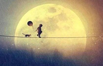 disegno di un bambino e un gatto in equilibrio su un filo con la luna dietro