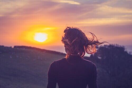 Donna che guarda il tramonto in montagna