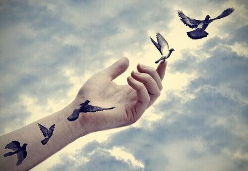 Mano tatuata con uccelli