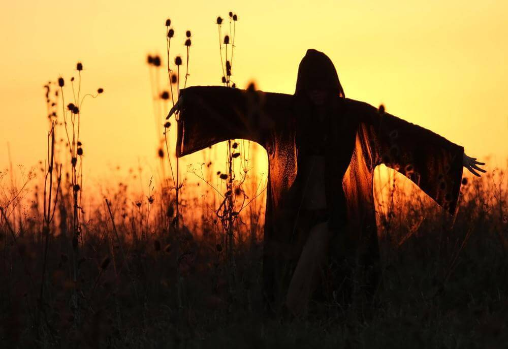 Donna con mantello al tramonto