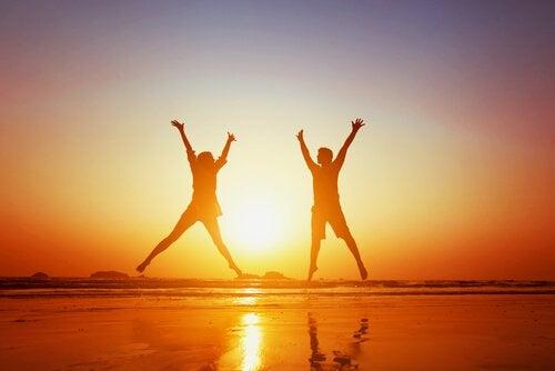 coppia felice che salta in spiaggia