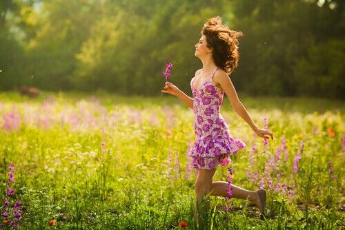 donna felice e che sorride tra i fiori
