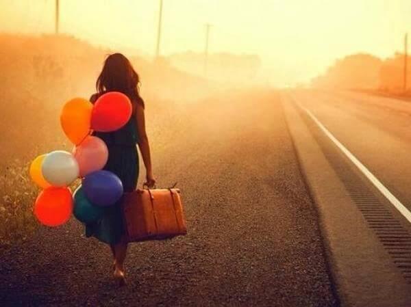 ragazza ha paura ma va via con valigia e palloncini colorati