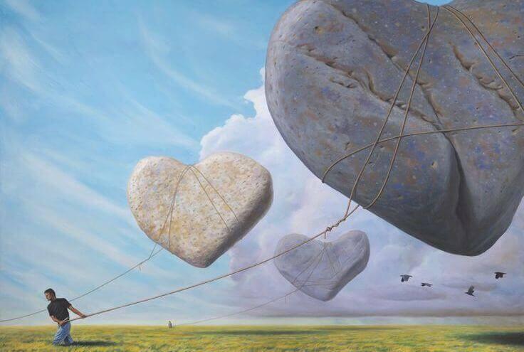 uomo tira con una corda sassi a forma di cuore sospesi in aria
