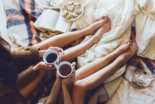 amiche sul letto bevono caffè