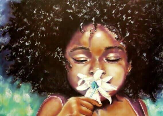 bambina di colore che annussa un fiore