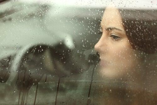 donna guarda fuori da finestrino appannato