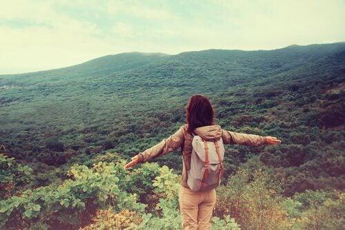 ragazza in un bosco con le braccia aperte