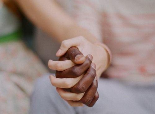 mano bianca e nera che si stringono