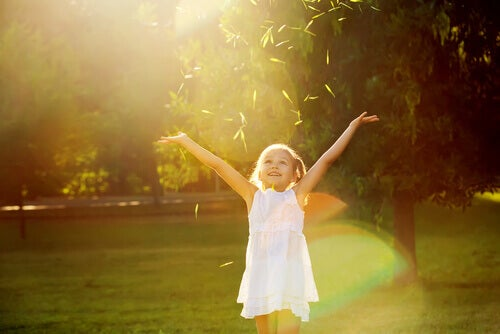 Bambina-felice-in-un-prato-con-le-braccia-aperte