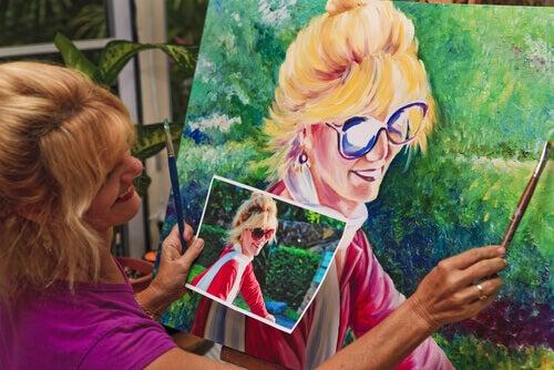 donna bionda dipinge quadro guardando foto