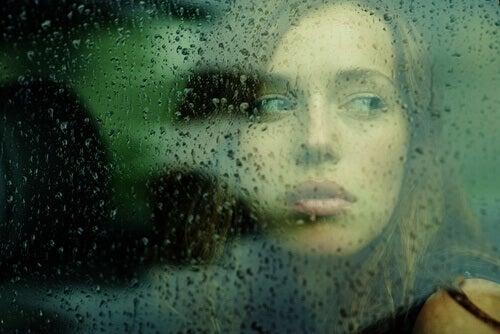 Donna-che-guarda-attraverso-un-vetro-con-gocce-di-pioggia