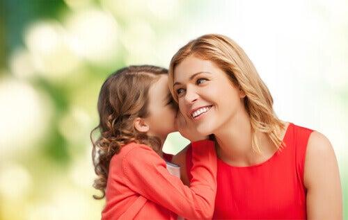 bambina parla orecchio della madre