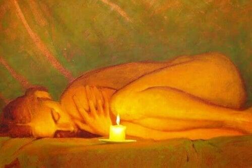 donna accovacciata vicino ad una candela