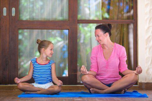 madre che insenga alla figlia a meditare