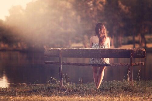 ragazza seduta su una panchina di fronte al lago