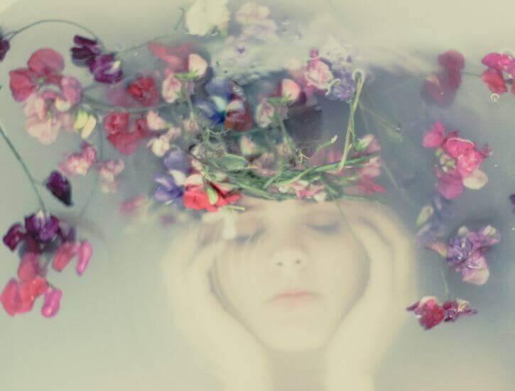viso di donna sott'acqua e fiori