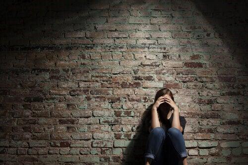 Donna triste appoggiata al muro