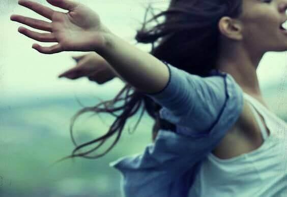 ragazza alza le mani al cielo