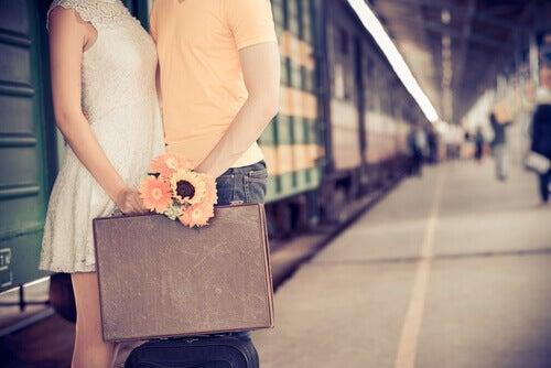 coppia alla stazione dei treni, valigia e mazzo di fiori