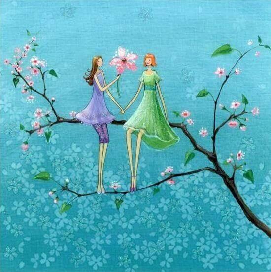 amiche in piedi su un ramo tra i fiori rosa