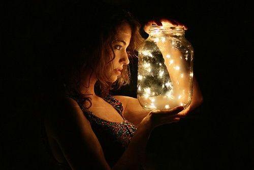 donna tiene in mano vaso con lucciole