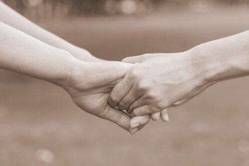 due persone si tengono per mano il perdono