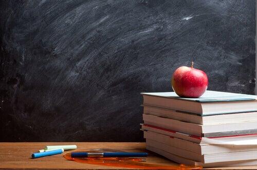 lavagna, libri, mela e penne