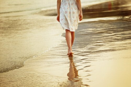 ragazza che passeggia sulla battigia