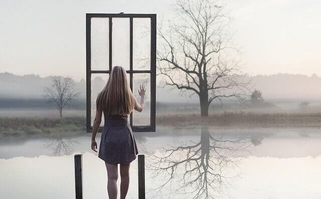 ragazza difronte a lago e finestra sospesa in aria