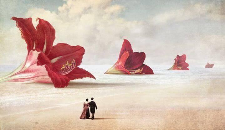uomo e donna camminano su spiaggia con fiori rossi giganti