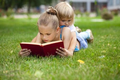 Bambine che leggono sul prato
