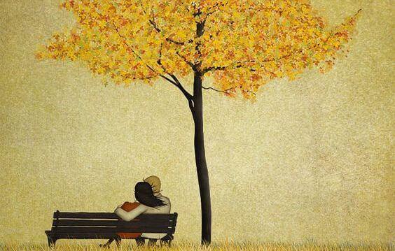 coppia seduta su panchina si abbraccia