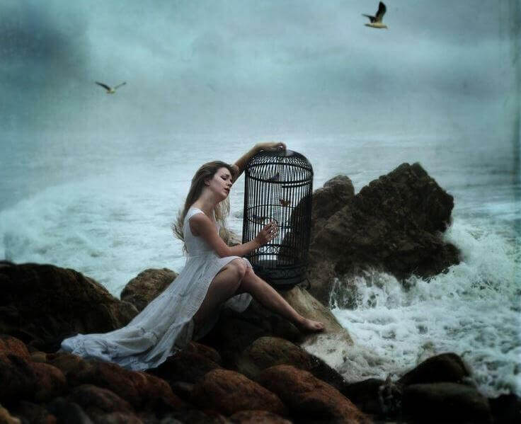 donna sugli scogli con gabbia in mano