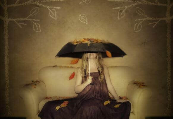 Donna sul divano che-si-copre-con-ombrello