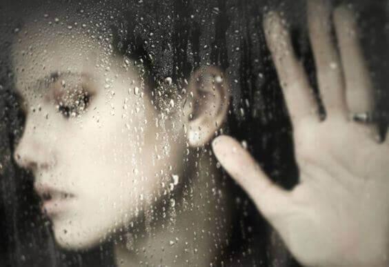 Donna con vetro e pioggia