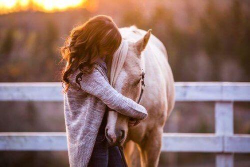 donna che abbraccia un cavallo
