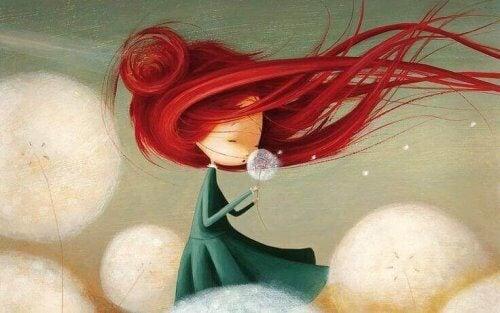 bambina con i capelli al vento e un soffione in mano