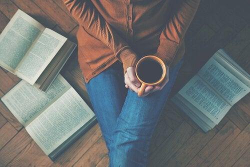 donna-beve-caffe-seduta-a-terra-con-libri