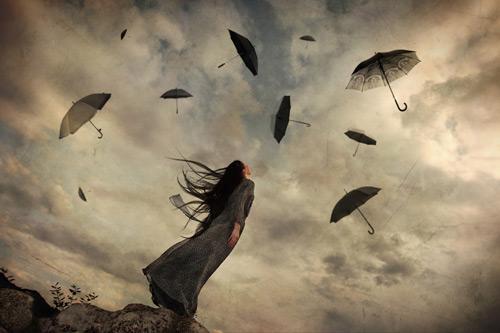 donna che guarda ombrelli che volano