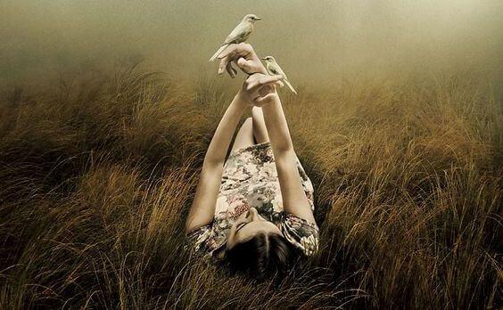 donna sdraiata con uccelli in mano