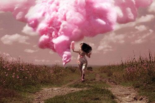 ragazza che corre davanti una nuvola rosa
