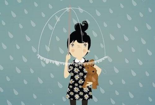 bambina con ombrello e cane in braccio