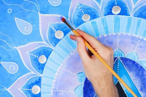 mano che colora un mandala blu