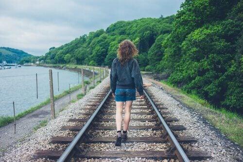 ragazza cammina sulle rotaie