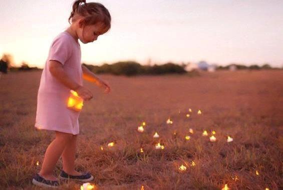 bambina che raccoglie luci in un campo