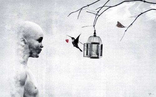 colibrì fuori dalla gabbia con cuore che pende dal becco