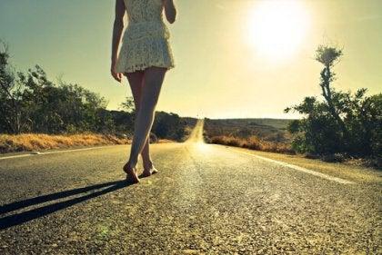 Donna che cammina sulla strada a piedi nudi