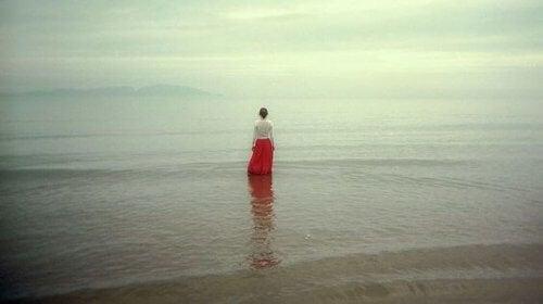 donna sulla battigia che guarda l'orizzonte